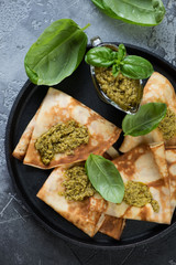 Above view of stuffed crepes with basil pesto in a frying pan, studio shot