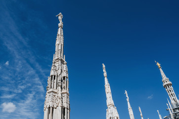 Sculptures, statues and architectural elements on the top of Duomo Cathedral, main tourist attraction of Milan, Italy. Scenic vertical travel postcard.