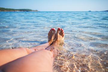 Woman legs on the beach.