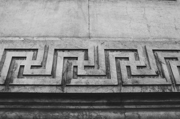 Swastika continuous ornament, carved on a stone wall. Black and white picture.