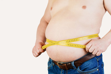 The belly of a fat man isolated on white background. Fat man holding a measuring tape. Weight Loss.