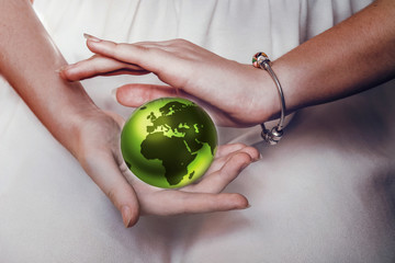 Green planet Earth in female hands