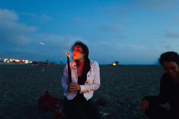 Woman blowing the firewood at beach to start bonfire, San Francisco, California