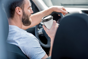 Handsome man dressed cassual in white t-shirt driving a car with coffee to go