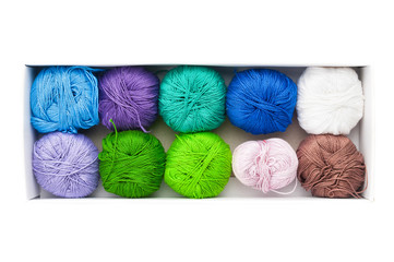 Colored balls of yarn in box on white background