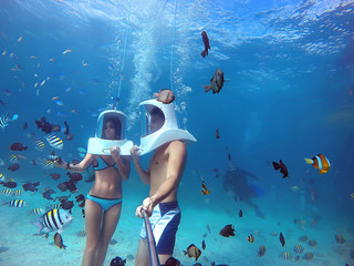 Loving couple goes helmet diving together in tropical sea of Boracay during honeymoon and makes selfie on gopro