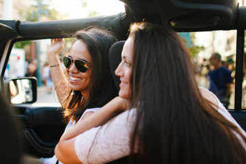20-something females laugh together in open top jeep on California road trip