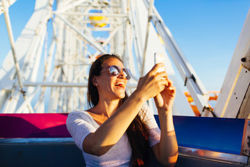 Woman taking pictures while in amusement park ride
