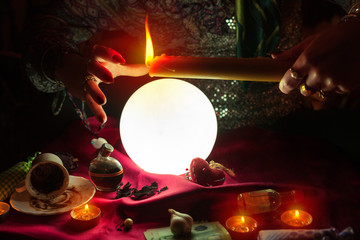 Candle in hand of fortune teller woman above crystal ball