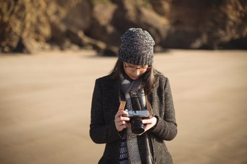 Woman looking at photos on digital camera at beach