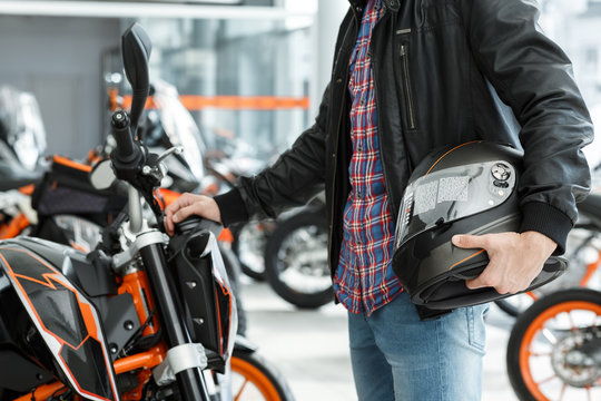 Important detail. Cropped shot of a man wearing leather jacket standing near his newly bought motorbike holding a black helmet at the motorcycle salon