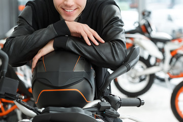 Important life safety. Cropped closeup of a young handsome man smiling cheerfully posing on his new motorcycle leaning on a helmet