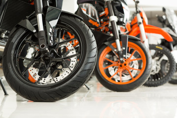 Riders will love. Cropped shot of the wheels of motorbikes standing in the line at the motorcycle salon
