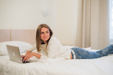 A cute young woman smiling excitedly at her laptop screen. She is relaxing in bed.