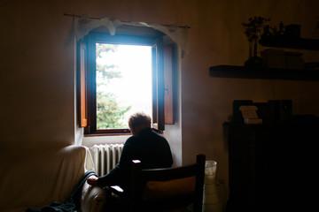 woman Indoors sitting facing window Tuscany Italy.