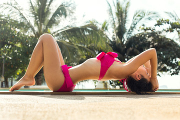 Sexy girl in a swimsuit lies on the edge of the pool
