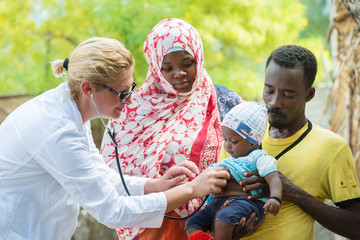 Female Caucasian doctor listening breath and heart beat of little African baby with stethoscope.Father holding the baby, mother looking at baby
