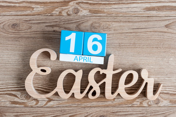 Easter carved wooden inscription with cubes calendar April 16th. Holiday background. day 16 of month