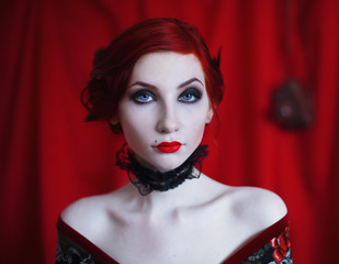 A woman with red curly hair in a black dress and retro makeup on a red background. Red-haired girl with pale skin, blue eyes, a bright unusual appearance, red lips and a fatal face. Noir woman