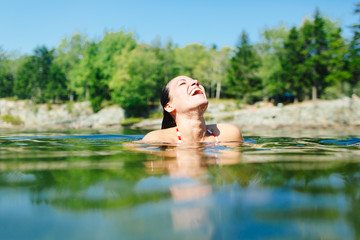Young woman swimming in lake