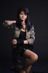 Young pretty female model with AKS-74 (Kalashnikov) assault rifle in studio
