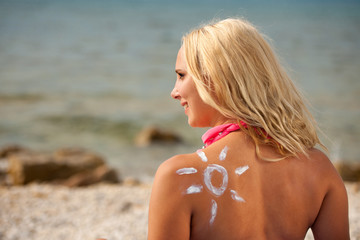 Young woman with sun shape on the shoulder relaxing  on the beach