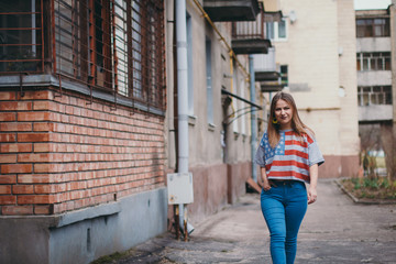 A hipster girl in an old courtyard posing and smiling