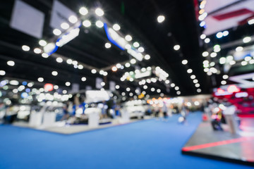Blurred, defocused background of public event exhibition hall showing cars and automobiles, business commercial event concept