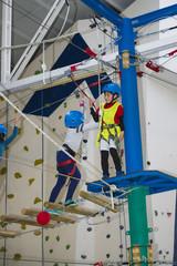Niño entrenando deporte extremo de escalada y montañismo en unas instalaciones cerradas y seguras