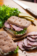 Rye bread sandwich with ham, salad and cucumber. On wooden cutting board and table.