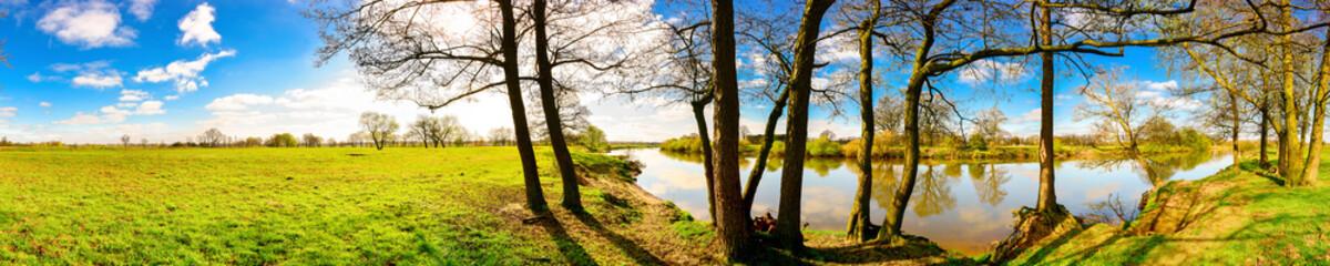 Panorama einer Landschaft im Frühling mit blauen Himmel, Sonne, Wiese und Fluss