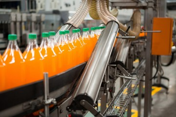 Orange drink bottles on production line in factory