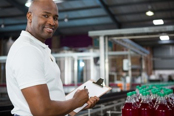 Smiling male worker noting about products in juice factory