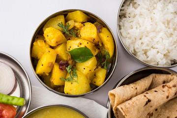 indian typical stainless steel lunch box or tiffin with north indian or maharashtrian food menu like chapati//roti, dal tadka, white rice and aloo / potato sabji / gobi or cauliflower sabji with salad