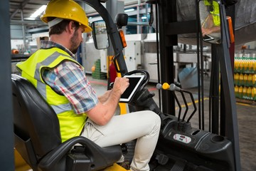 worker using tablet while sitting on forklift