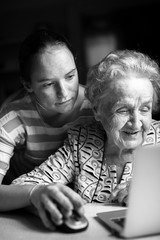 Girl teaches her grandmother to working on the computer. Black-and-white photo.