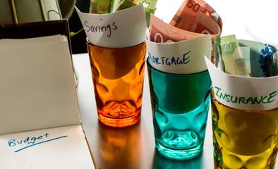 Budget Glass Jars with Money Balancing Insurance Mortgage and Savings