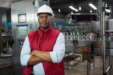 Confident male employee standing in manufacturing industry