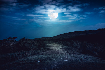 Landscape in nature of beautiful full moon behind cloud and roadway.