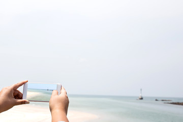 hand hold and touch screen smart phone,cellphone over blurred beautiful beach background