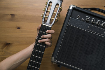 Guitar amplifier and woman hand holding a guitar on wood table