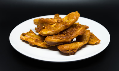 Delicious traditional golden fried banana fritters on white plate with black background isolated