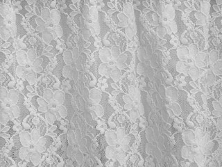 White fabric lace with small flowers on the white background