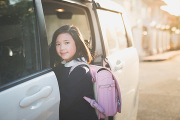 Asian girl in student uniform going to school by car under sunlight