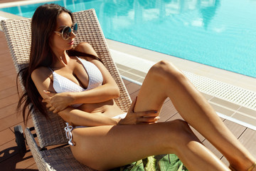 Sexy Woman In Bikini Sunbathing Near Pool In Summer