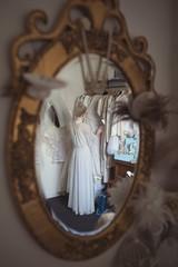 Reflection of bride selecting wedding dress