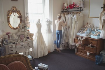 Young woman selecting wedding dress from clothes hanger