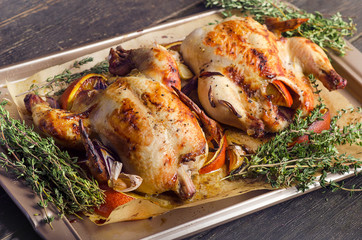 Roasted whole chicken with oranges and herbs on a dark wooden background