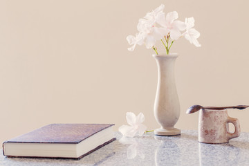 white flowers, cup of coffee and book on table