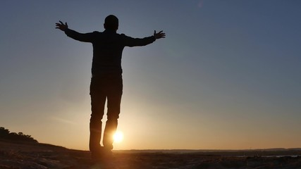 freedom. Man stands on a cliff sunset silhouette hand in the sides lifestyle